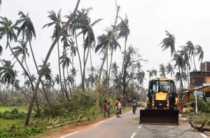 Earthmovers clear the road after Cyclone Fani, one of the biggest to hit India in years
