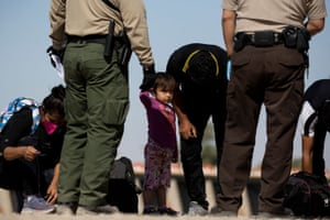 A girl watches as migrants from Guatemala remove their shoelaces as they are initially processed after turning themselves over to authorities at the US-Mexico border in Arizona