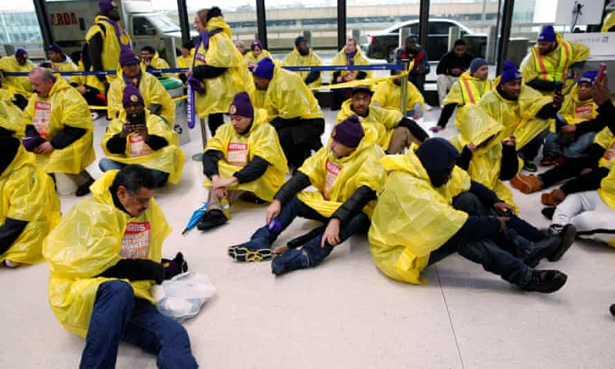 People sit in a terminal during a Fight for $15 wage protest at Newark International Airport in New Jersey Tuesday.