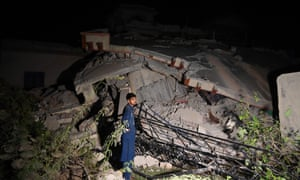 A Pakistani man stands beside a collapsed building following an earthquake on the outskirts of Mirpur.