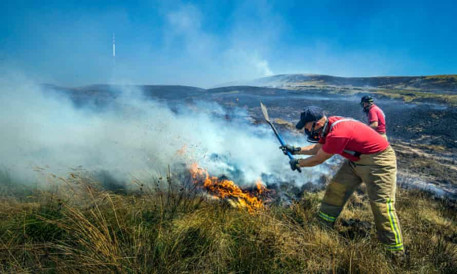Firefighters work to put out the fires on Winter Hill, near Bolton.