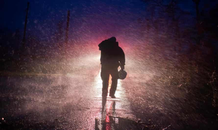 Montegut fire chief Toby Henry walks back to his fire truck in the rain as firefighters cut through trees on the road in Bourg, Louisiana, as Hurricane Ida passes.