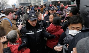 Police officers push away supporters of rights lawyer Pu Zhiqiang and foreign journalists near the Beijing Second Intermediate People's Court in Beijing on Monday.