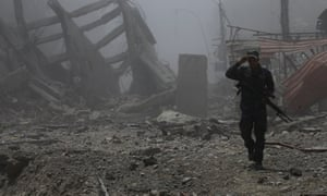 A member of the Iraqi Federal police walks past destroyed buildings from clashes in Mosul.