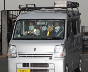 A masked man, center, believed to be former Nissan Chairman Carlos Ghosn, leaving Tokyo's Detention Center.