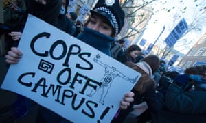 A protester holds a sign reading 'cops off campus'