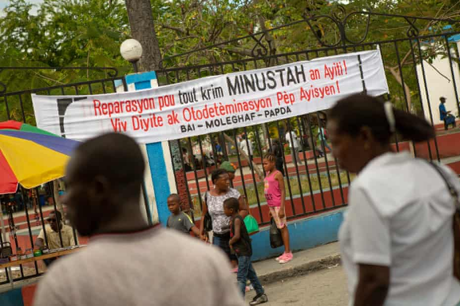 A sign strung in Mirebalais calls for reparation for the 'crimes' of the UN in Haiti