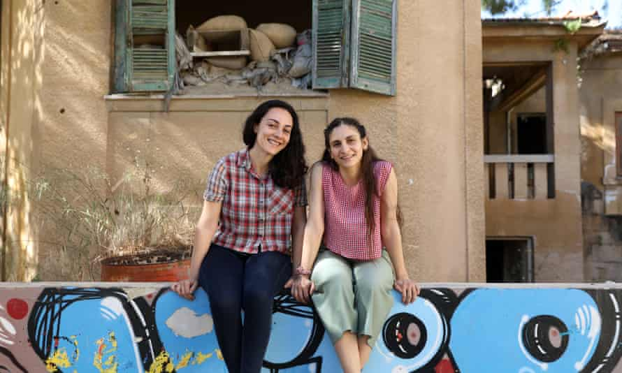 Feray Yalcuk and Maria Loucaidou sitting side by side and smiling, on a wall with grafitti on it and with a shabby building with broken shutters behind them