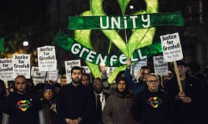 Local people standing holding placards stating 'Justice for Grenfell' during the monthly silent march for the Grenfell Tower fire victims, London, 14 November 2017