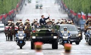 马克龙从一辆军车上挥手。