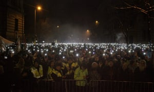 Protesters against the 'slave law' light their mobile phones in front of the parliament building in Budapest