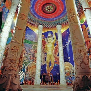 A large reception space at the underground temples of Damanhur in Italy. The wall is covered in a brightly painted human figure mural.