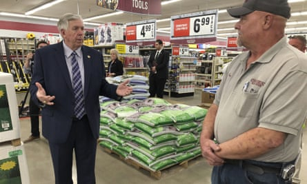 Missouri Governor Mike Parson, left, visits a hardware store in May.