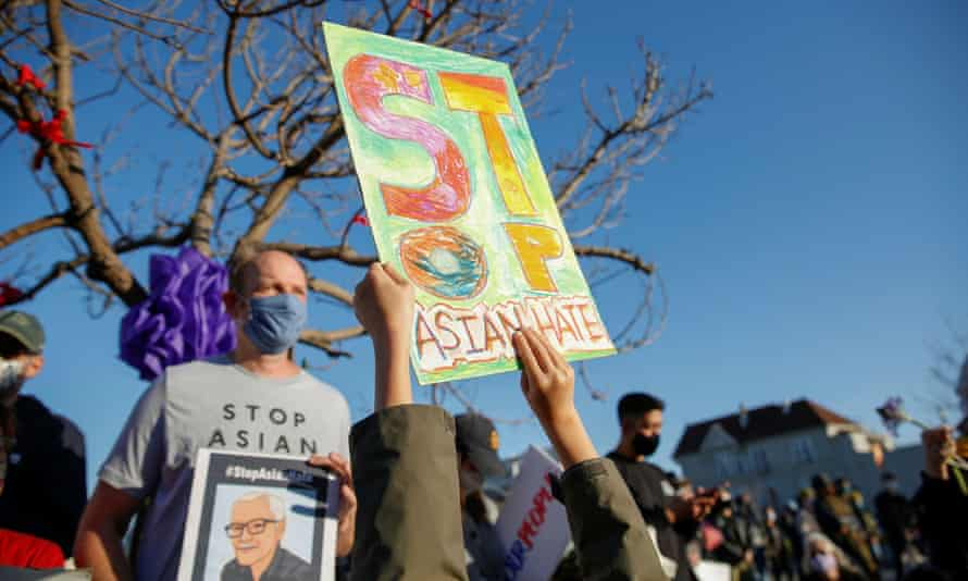 A six-year-old holds up a hand-drawn sign that reads 'Stop Asian hate' in Oakland, California, on 23 March.