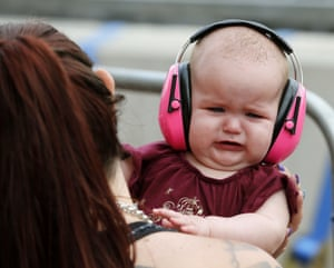 A baby seems to struggle with the noise of the racing trackside during the Newcastle 500's Supercars Race 23 at the Newcastle Street Circuit