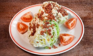 Iceberg wedge salad with chicken and bacon topping and quarters of tomato around the plate