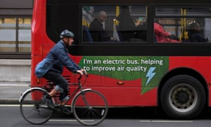 A cyclist rides past an electric bus in London.