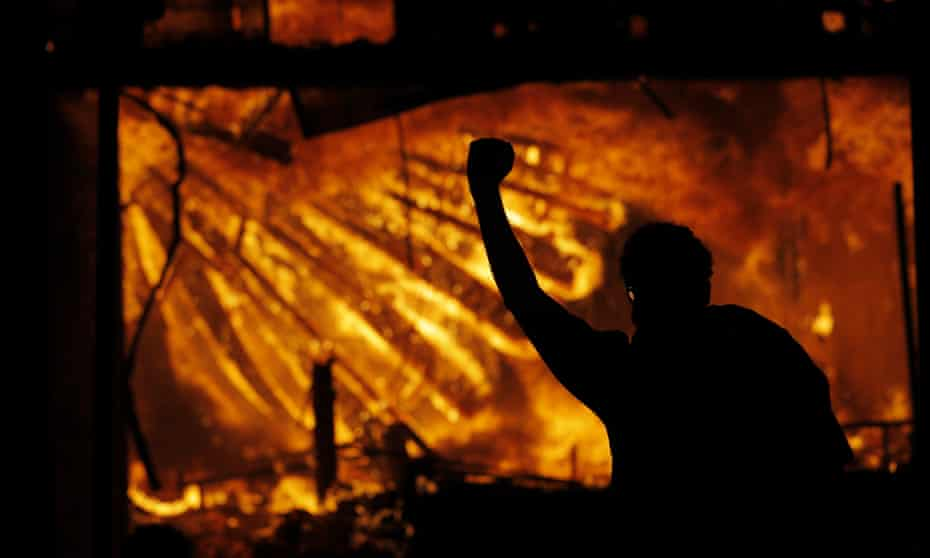 In this May 28, 2020 file photo, a protester gestures in front of the burning 3rd Precinct building of the Minneapolis Police Department in Minneapolis