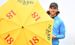 England's Tommy Fleetwood looks out from behind an umbrella at the sixth hole.