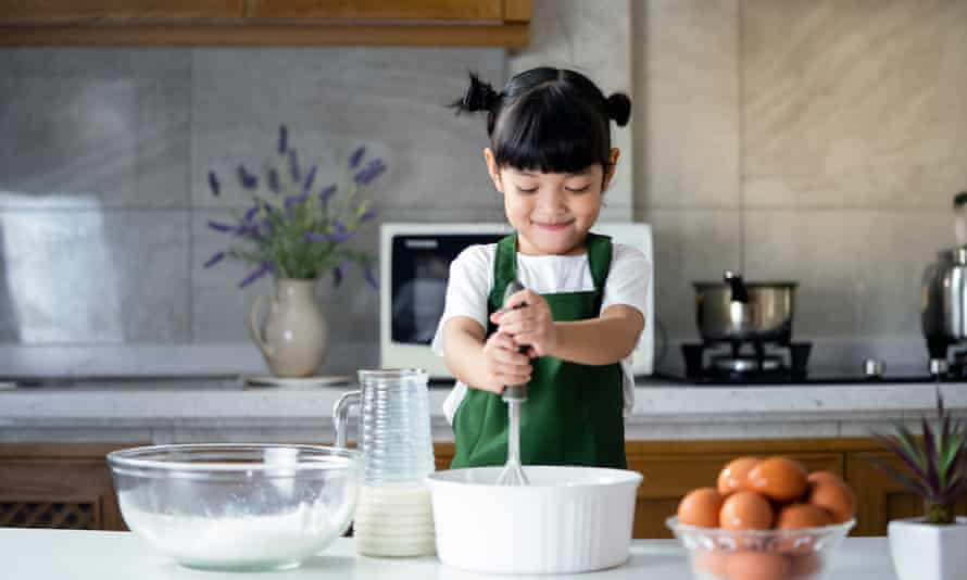 Young girl cooking with flour, milk and eggs in the kitchen