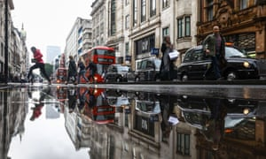 shoppers, taxis and buses mirrored in a puddle-strewn Oxford Street in London