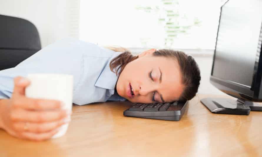 Sleeping woman in an office holding coffee