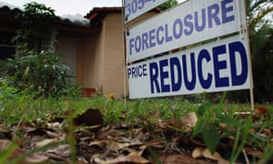 A foreclosure/price reduced sign stands at a home for sale in Miami, Florida.