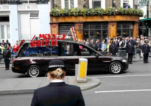 Police officers line the street as the coffin is transported in a hearse towards Southwark Cathedral for Palmer's funeral