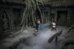A couple pose for their pre-wedding photos in an interior made to look like Angkor Wat