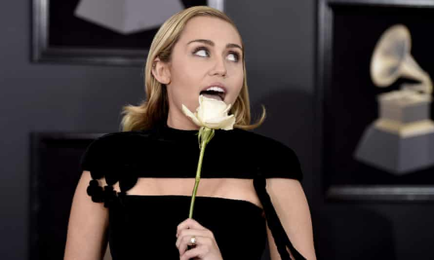 Miley Cyrus holds a white rose as she arrives at the Grammy awards last month