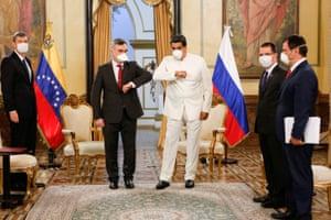 Venezuela's president, Nicolás Maduro, and the Russian ambassador Sergey Melik-Bagdasarov, bump elbows at Miraflores Palace in Caracas
