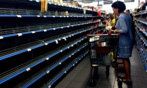 Shoppers stand in empty aisle