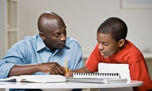 A man helps a boy with his homework
