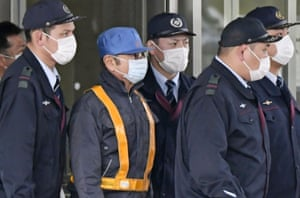 A masked man, center, believed to be former Nissan Chairman Carlos Ghosn, leaves Tokyo's Detention Center in Tokyo, Wednesday, March 6, 2019. Ghosn was released Wednesday after putting up 1 billion yen ($8.9 million) in bail.(Kyodo News via AP)