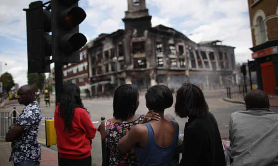 Residents watch as a building burns after riots on Tottenham High Road on 7 August 2011.