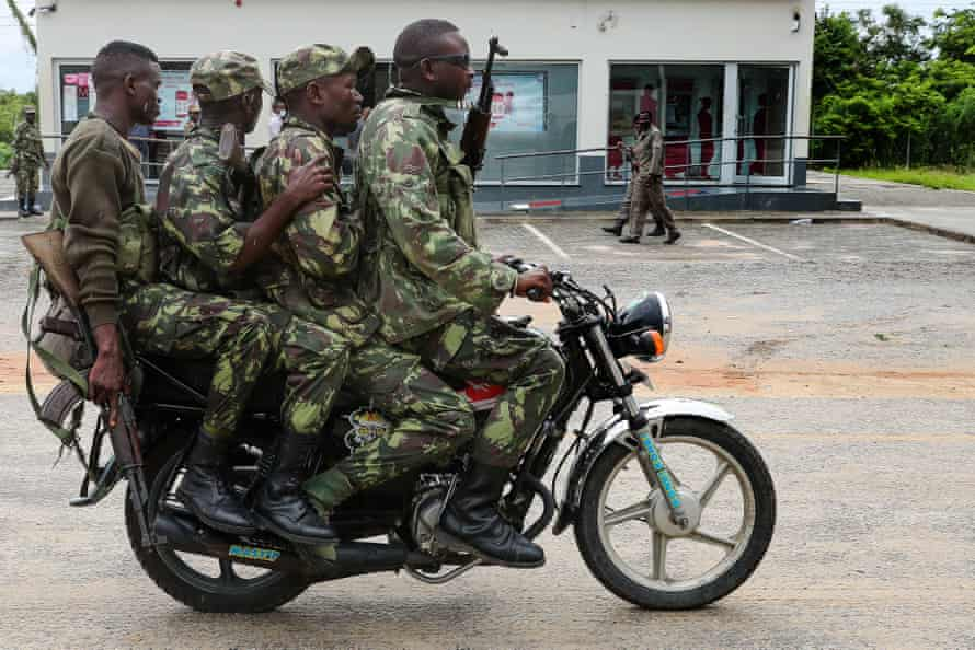 Mozambique army soldiers take a ride on a motorbike in the streets of Palma, Cabo Delgado.