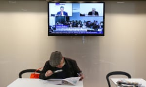 A man uses a magnifying glass to study his horse racing form guide in a newspaper in a cafe as Australian Opposition Leader Bill Shorten is shown on a television giving evidence at the Royal Commission into Trade Union Governance and Corruption in Sydney. Wednesday, July 8, 2015