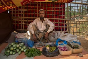 Sultan Ahmed, 60, sells beans, onions, garlic and other vegetables from his stall in the camp