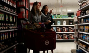 Solveig Woo and daughter Katherine shop for supplies inside a darkened Target store during Pacific Gas & Electric's power shutoff in Novato, California.