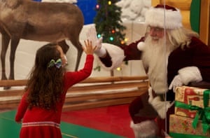 COVID-19: Santa Behind Glass, Hudson, Massachusetts, USA - 06 Dec 2020Mandatory Credit: Photo by Allison Dinner/ZUMA Wire/REX/Shutterstock (11254680a) Children wearing masks visit a Santa Clause behind plexi-glass at a Cabelas retail store during the COVID-19 pandemic. COVID-19: Santa Behind Glass, Hudson, Massachusetts, USA - 06 Dec 2020