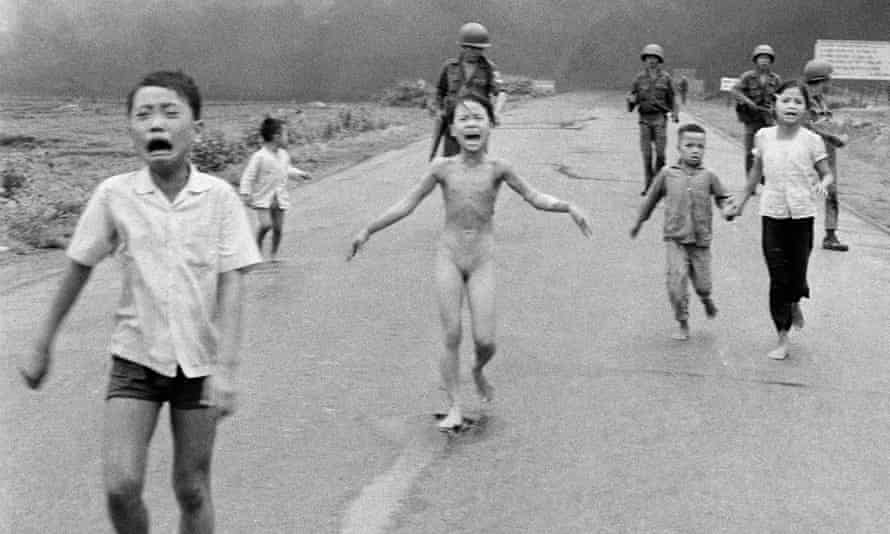 South Vietnamese forces follow terrified children, including Kim Phuc (C) as they run away after a napalm attack.