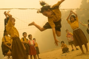Children play without wearing any protection from the haze