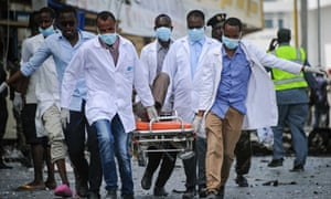 Paramedics use a stretcher to carry a victim from the scene of the car bomb attack in Mogadishu.