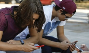 Youth check their cell phones in Sao Paulo, Brazil