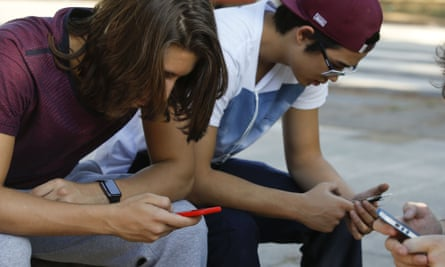 Teenagers check their mobiles in São Paulo, Brazil