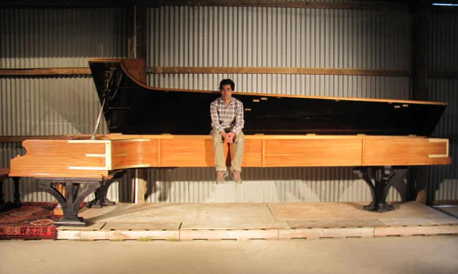 Adrian Mann with his 5.7m-long piano in Dunedin, New Zealand.