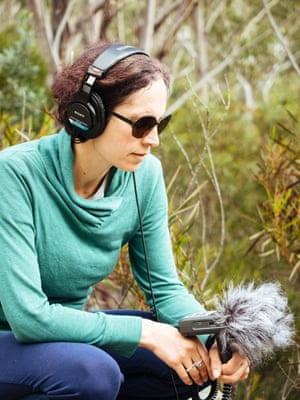 A woman in headphones holding a microphone crouching in a forest