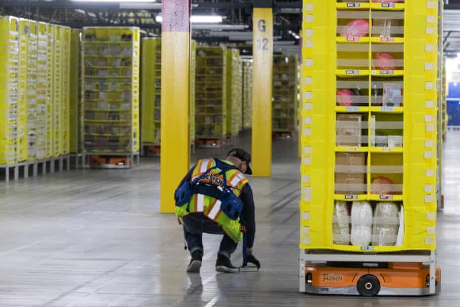 A worker retrieves a book that fell off a pod at the Amazon fulfillment center in New York.