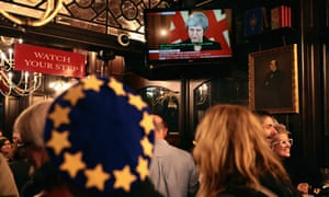 An anti-Brexit campaigner watches a live broadcast of the prime minister, Theresa May, delivering a speech from No 10 after a day of high drama in Westminster