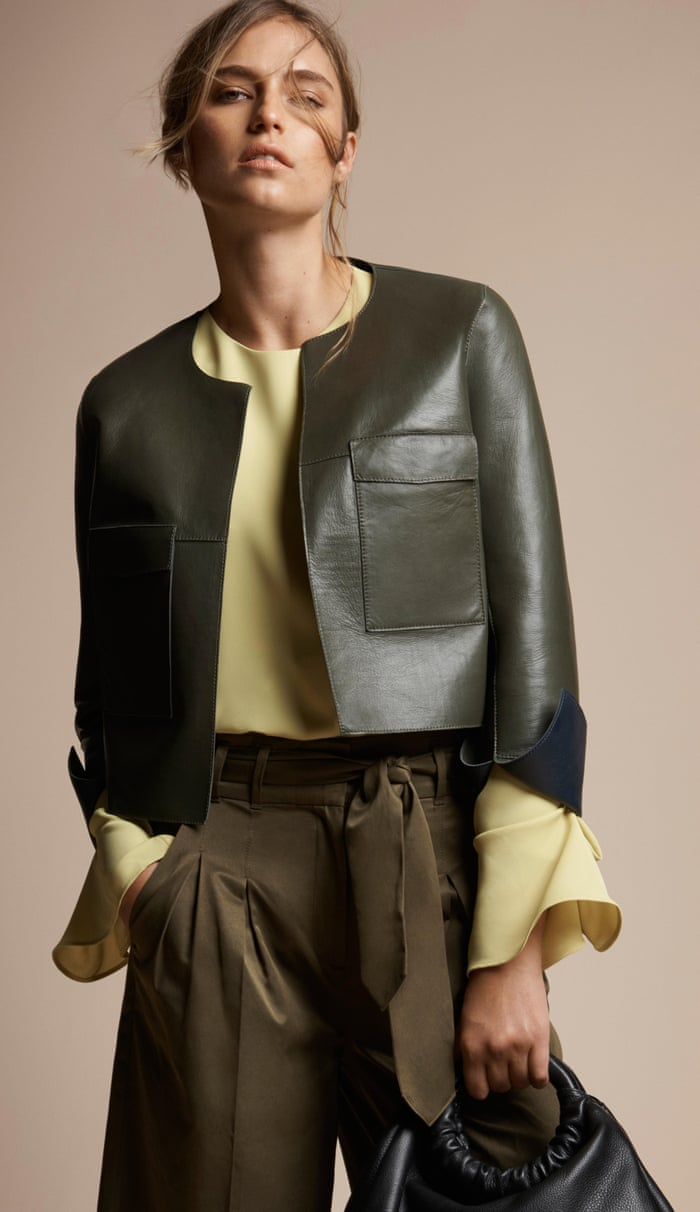 A model wears a leather jacket, blouse and trousers in earthy tones.